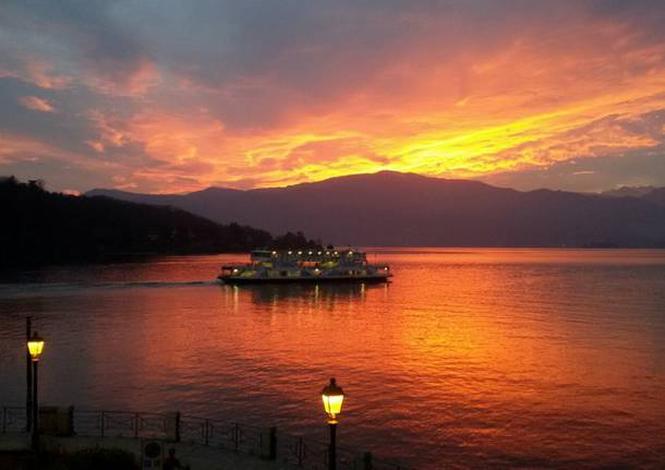 Il traghetto nel lago infuocato dal tramonto