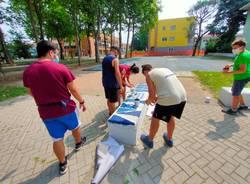 Giovani saronnesi al lavoro per dipingere le panchine del Matteotti